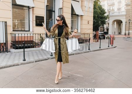 Full-length Portrait Of Stunning Female Model Talking On Phone While Carrying Bags Down The Street.
