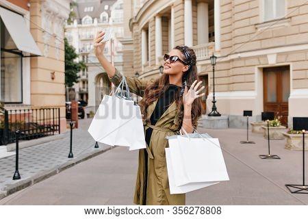 Graceful Fashionista Girl Wears Green Coat Making Selfie On The Street. Attractive Brunette Woman Wi