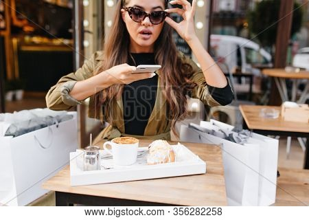 Latin Dark-haired Woman Taking Picture Of Her Lunch, Sitting In Cafe After Shopping. Elegant Fashion