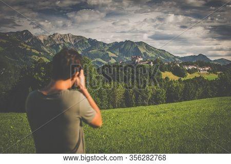Photographer taking photos of the splendid medieval village of Gruyères, Switzerland