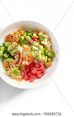 Poke with tuna and noodles. Hawaiian salad with avocado and tofu top view. Traditional polynesian dish with rice and cheese. Delicious native cuisine. Meal served with edamame, vegetables and soybean
