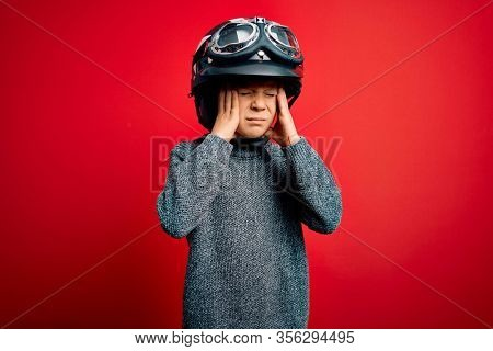 Young little caucasian kid wearing vintage biker motorcycle helmet and googles over red background suffering from headache desperate and stressed because pain and migraine. Hands on head.