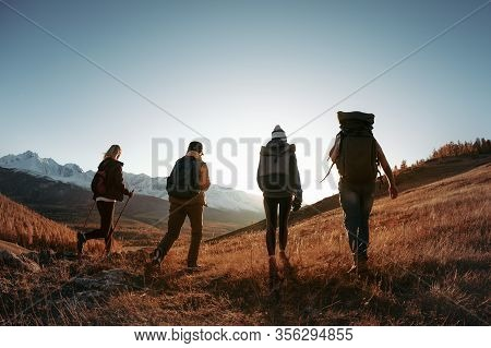 Four Unrecognizable Hikers Or Backpackers Walks With Backpacks In Sunset Mountains. Trekking In Moun