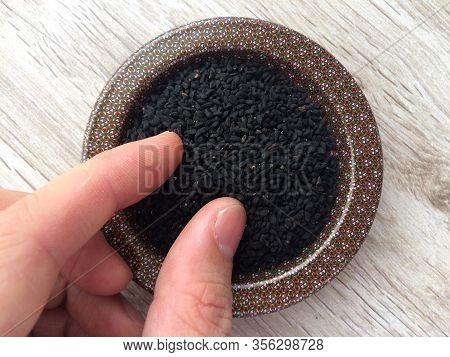 Close Up Of Nigella Seeds / Black Cumin / Black Onion Seed/ Black Sesame Seed With Male Hand. Tradit