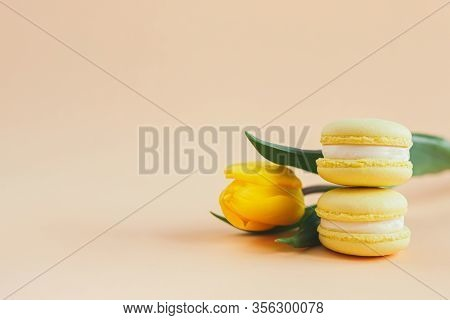 Tasty French Macarons With Yellow Tulip On A Peach Pastel Background. Lemon Macarons. Place For Text