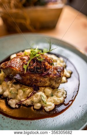 Grilled Pork Chop Or Cutlet, Demi Glace, Gnocchi With Sheep Cheese On Blue Plate