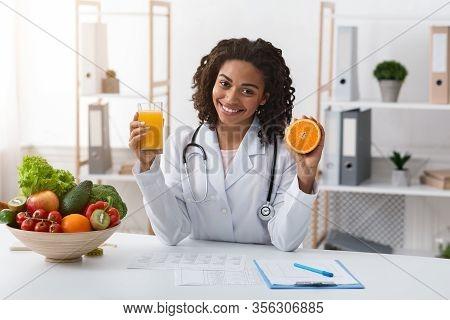 Cheerful Female Nutritionist African Woman Holding Fresh Orange Juice And Orange Half In Her Hands W