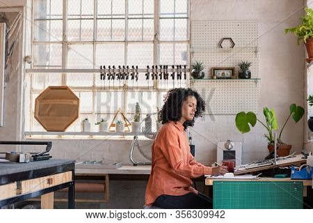 Young Woman Working At A Desk In Her Framing Workshop