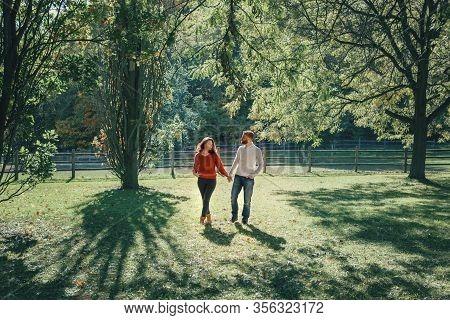 Happy Couple Man And Woman In Love Walking In Park Outdoor. Lovely Beautiful Caucasian Heterosexual