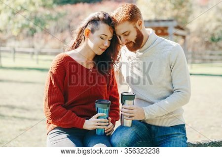 Happy Couple Man And Woman In Love Sitting In Park Outdoor. Lovely Beautiful Caucasian Heterosexual