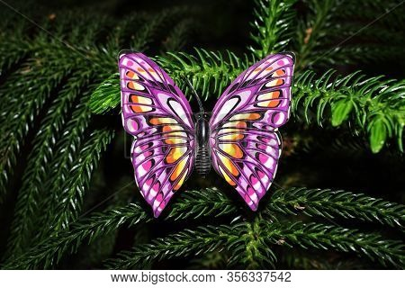 Beautiful Purple Butterfly Figurine Decoration On Real Natural Christmas Tree Plant. Close Up Of Pur