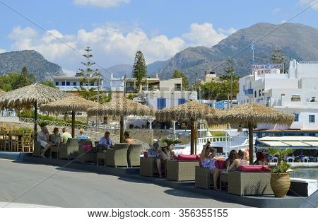 Sissi, Crete, Greece - June 11, 2019 : Restaurant Over Looking Sissi Harbour With A View Of The Moun
