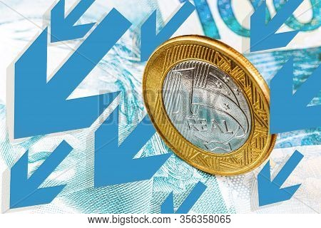 Brazilian Money, Banknotes And Coins, With Arrows And Graphs. Concept Of Brazil's Financial Crisis,