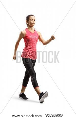 Full length shot of a serious young woman in sportswear walking fast isolated on white background