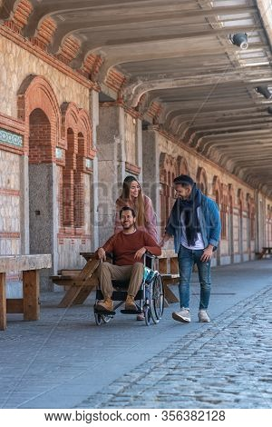 Paralyzed Young Man In A Wheelchair Accompanied By A Young Man And A Girl Strolling