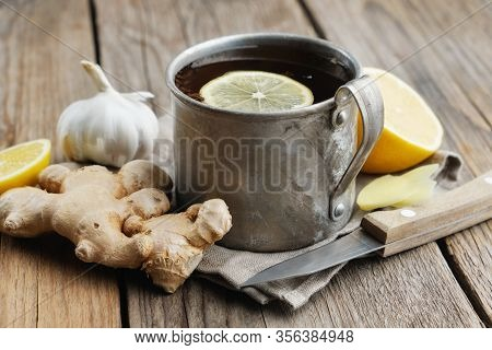 Ginger Tea Cup With Lemon, Ginger Roots, Garlic And Knife On Wooden Kitchen Table.