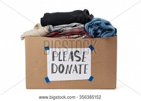 Large Brown Cardboard Box With The Inscription Please Donate, Box Is Filled With Various Clothes And