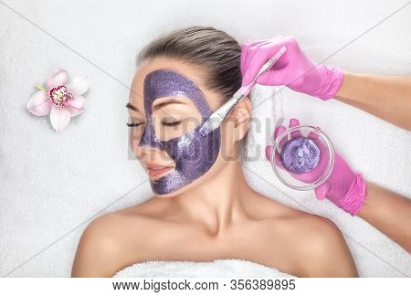 Beautician Makes A Face Mask With Purple Particles On The Face Of A Woman To Rejuvenate The Skin. Co