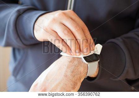 man hands disinfecting smart watch, eliminating germs coronavirus bacteria