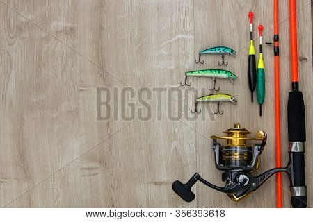 Color Spinner Lures, Fishing Bytes, Floats, Spinning Reel And Orange Rod On Wood. Place For Text. To