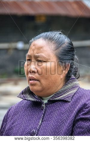 Guilin, China - May 10, 2010: Downtown. Facial Closeup Of Graying Woman With Purple Shirt.