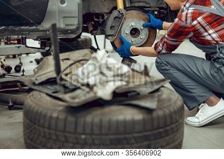 Young Female Mechanic Replacing The Brake Shoes