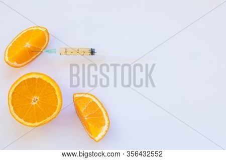 High Dose Vitamin C, Ampule For Injection. Syringe In Fresh Juicy Orange Fruit Slides. Concept Of Vi