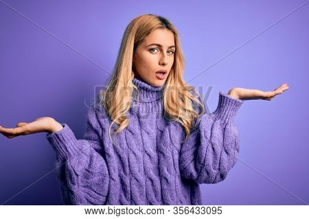 Young beautiful blonde woman wearing casual turtleneck sweater over purple background clueless and confused with open arms, no idea concept.