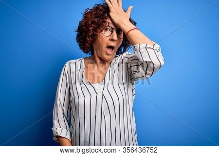Middle age beautiful curly hair woman wearing casual striped shirt over isolated background surprised with hand on head for mistake, remember error. Forgot, bad memory concept.