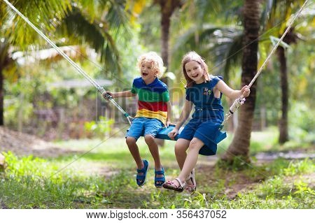 Kids On Swing. Children Swinging On Playground In Tropical Resort With Coconut Palm Trees