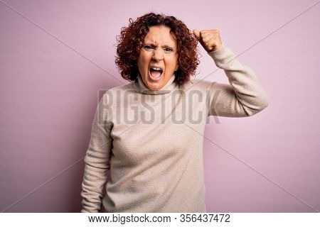 Middle age beautiful curly hair woman wearing casual turtleneck sweater over pink background angry and mad raising fist frustrated and furious while shouting with anger. Rage and aggressive concept.