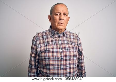 Senior handsome man  wearing casual shirt standing over isolated white background with serious expression on face. Simple and natural looking at the camera.