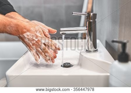 Washing hands with soap and warm water for 20 seconds for corona virus COVID-10 prevention. Work man for corona virus hygiene to stop spreading coronavirus.
