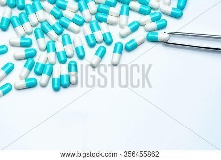Forceps Pick White-blue Capsule From Group Of Capsule Pills. Drugs Choose. Antibiotic Drug Selection