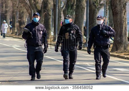 Uzhgorod, Ukraine - March 18, 2020: Police Officers In Medical Masks Patrol The City Center During Q