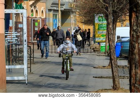 Uzhgorod, Ukraine - March 18, 2020: A Boy In A Medical Mask Rides A Bicycle In The City Center Durin