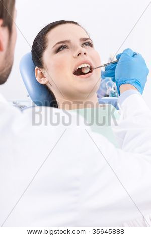 Dentist meticulously examines the oral cavity of the patient on the dentist's chair