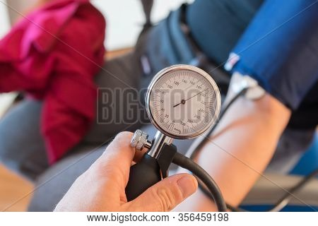 Analog Sphygmomanometer In The Foreground Detects Human High Blood Pressure. Hypertension Concept An