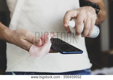 A Man Splashes On Smartphone A Sanitizer To Disinfect And Prevent Viral Diseases. Antibacterial Anti