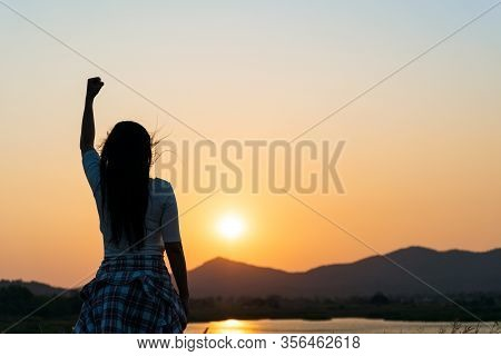 Soft Focus Of Woman With Fist In The Air During Sunset Sunrise Mountain In Background. Stand Strong.