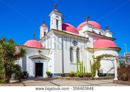 The Jerusalem Orthodox Church. Place of worship and pilgrimage. Israel. Capernaum. Snow-white church building with pink domes and golden crosses. The concept of religious pilgrimage