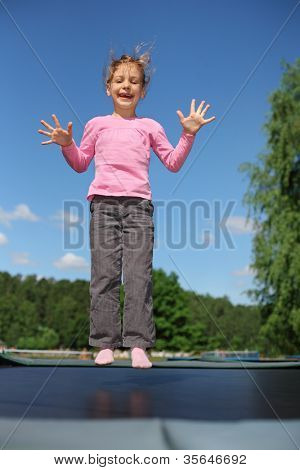 Joyful girl dressed in pink T-shirt jumps on trampoline at sunny summer day poster