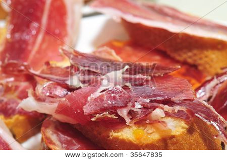 slices of bread with spanish serrano ham served as tapas poster