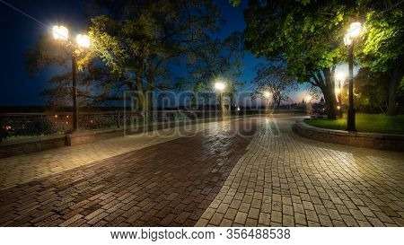 Empty City Park Landscape At The Late Evening Or Night With Lit Lightposts And Brick Road