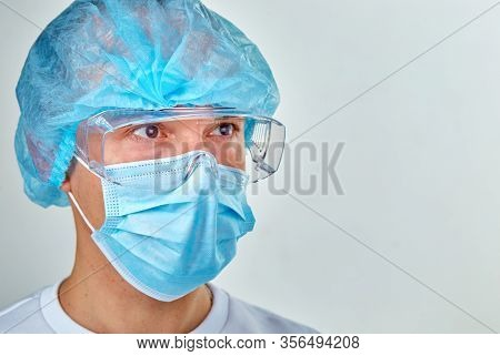 Doctor In Mask Is Looking Forward Portrait. Medical Background, Template, Wallpaper. Coronavirus Cov