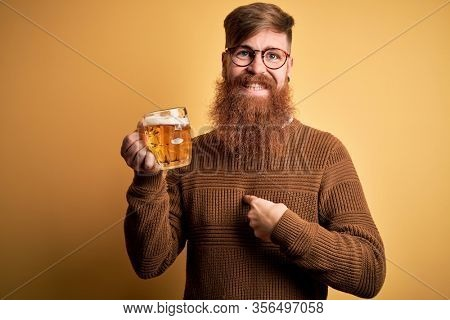 Irish redhead man with beard drinking a glass of refreshing beer over yellow background with surprise face pointing finger to himself