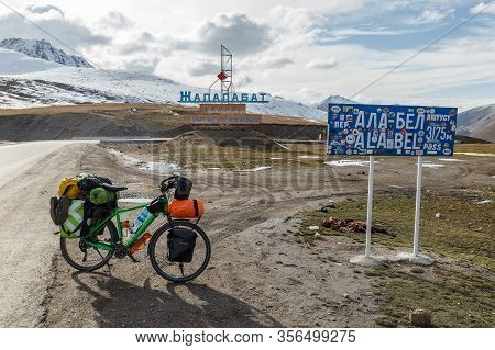 Chuy Province, Kyrgyzstan - October 07, 2019: A Tourist Bike With Bags Is Standing Near The Sign Of