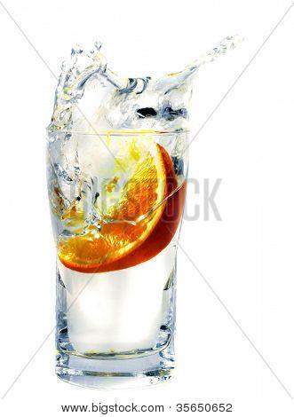 splashing orange into a water glass
