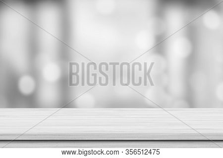 White Wood Tabletop Over Blur White Bokeh Light Background. Empty Wood Shelf For Product Display, Ba