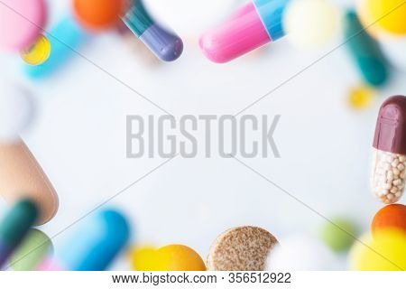 Colorful Pills Flying Above White Background With Framing And Levitation Effect.